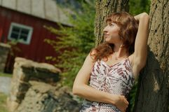 Girl Leaning Against Tree. Pretty girl leaning against a tree stock photography