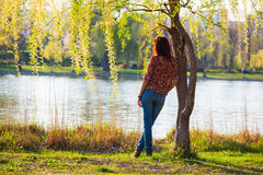 Girl leaning against a tree, pensive Stock Photo