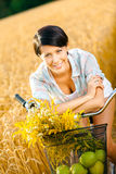 Girl leaning on bicycle in rye field Royalty Free Stock Photo