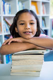 Girl leaning on books at table in school library Stock Photography