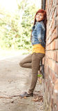 Girl leaning on the bricks wall Stock Image