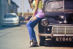 Girl leaning on classic car