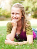 Girl Leaning on her Hand. Pretty teenage girl poses prone on the grass leaning on hand Royalty Free Stock Image