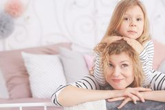 Girl leaning on mom`s head. Little girl leaning on her mom`s head royalty free stock photo