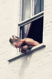 Girl leaning out of window Stock Image