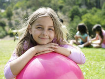 Girl (7-9) leaning on pink space hopper in park, smiling, portrait, focus on foreground Stock Photo