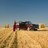 Girl leaning on retro car with straw bales background. Royalty Free Stock Photos