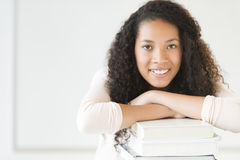 Girl Leaning On Stacked Books In Classroom Stock Photos