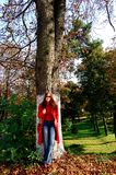 Girl leaning on tree. A picture of a girl leaning relaxed on a tree in city park Royalty Free Stock Image