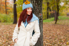 Girl leaning on tree in the park with falling leaves Royalty Free Stock Images