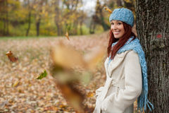 Girl leaning on tree in the park with falling leaves Royalty Free Stock Image