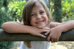 Girl leaning on wooden fence Stock Photo