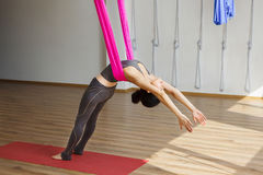 Girl leans back with hammock doing aerial yoga exercises. Girl leans back with help of hammock doing aerial yoga exercises in gym. Anti gravity position made Stock Image