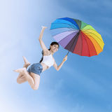 Girl leaps with a colorful umbrella outdoors Royalty Free Stock Photos