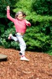 Girl leaps high in playground royalty free stock image