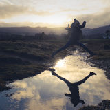 Girl Leaps Over Stream. A Teen Jumps Over Water On A Nature Hike Stock Image