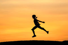 Girl leaps during sunset. Royalty Free Stock Photos