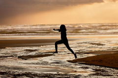 Girl leaps into the water. A girl in silhouette at sunset leaps into the creek on Nye Beach that flows into the ocean in Newport, Oregon Stock Photos