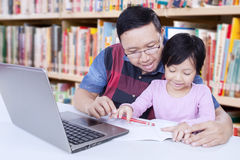 Girl learn to write in the library with a teacher. Image of lovely little girl studying in the library and learn to write on the book with a male teacher Royalty Free Stock Image