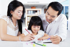 Girl learn to write with parents Royalty Free Stock Photos