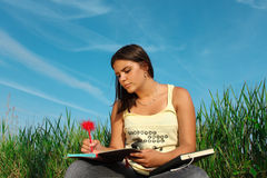 Girl learning. Young girl learning on meadow Royalty Free Stock Photo