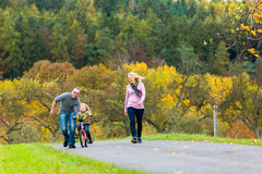 Girl learning bicycling in fall or autumn park. With parents Royalty Free Stock Photography
