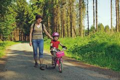 Girl learning biking. Mother learning his young daughter  how to ride a bike in summer Royalty Free Stock Image