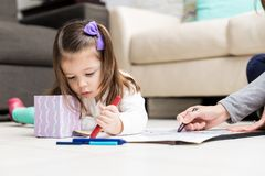 Girl Learning Drawing At Home. Pretty child and mother using crayons to draw on paper in living room stock image