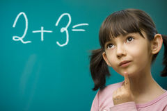Girl learning math. Schoolgirl stay near school blackboard. Close up Stock Photo