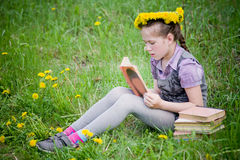 Girl learning in meadow. Girl reading learning book in dandelions meadow Royalty Free Stock Photography