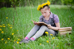 Girl learning in meadow Stock Image