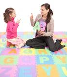 Girl learning phonics alphabet abc. Girl learning phonics alphabet and actions from teacher. Isolated on white Stock Image