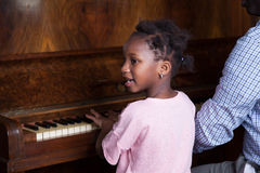 Girl learning play piano with her dad. Young girl learning play piano with herr father Royalty Free Stock Photo