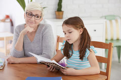 Girl learning reading with tutor. Girl learning reading with nice private tutor Royalty Free Stock Photography
