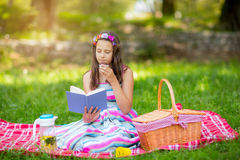 Girl learning on summer vacation and reading book Stock Image