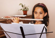 Girl learning to play the flute stock photo