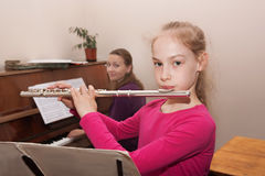 Girl learning to play the flute Stock Photography