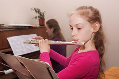 Girl learning to play the flute. A girl learning to play the flute and the teacher accompanies him Stock Photo