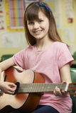 Girl Learning To Play Guitar In School Music Lesson Stock Photography