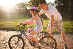 Girl learning to ride a bicycle with father in park Stock Photography