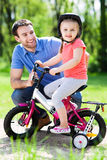 Girl learning to ride a bike with her father Stock Image