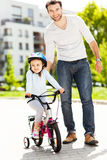 Girl learning to ride a bike with her father Stock Photo
