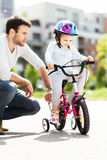 Girl learning to ride a bike with her father Stock Photos