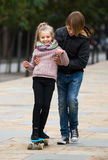 Girl learning to ride skateboard, teenage brother supporting he Royalty Free Stock Image