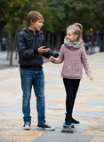 Girl learning to ride skateboard, teenage brother supporting he Royalty Free Stock Photos