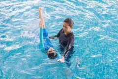 Girl learning to swim with coach. At the leisure center royalty free stock photography