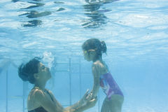 Girl learning to swim with mom Royalty Free Stock Images