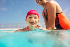 Girl learning to swim in the pool. Cute girl with swim cap learns to swim with mothers help in outdoor pool. Girl having swimming lesson with mother in pool stock photography