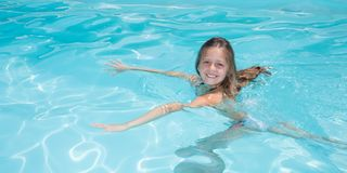 Girl learning to swim in swimming pool of city. Young girl learning to swim in swimming pool of city Royalty Free Stock Photo