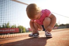 Girl learning to tie shoelaces. Little girl learning to tie shoelaces outside stock photography